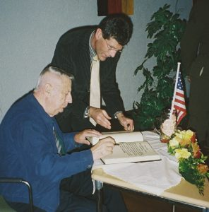 Major Baum signs the Golden Book of Gemuenden with the Mayor standing by.