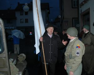 "Mayor Waldemar Horn of Rieneck with the white ""surrender"" flag talks with Sgt. Heinlein."